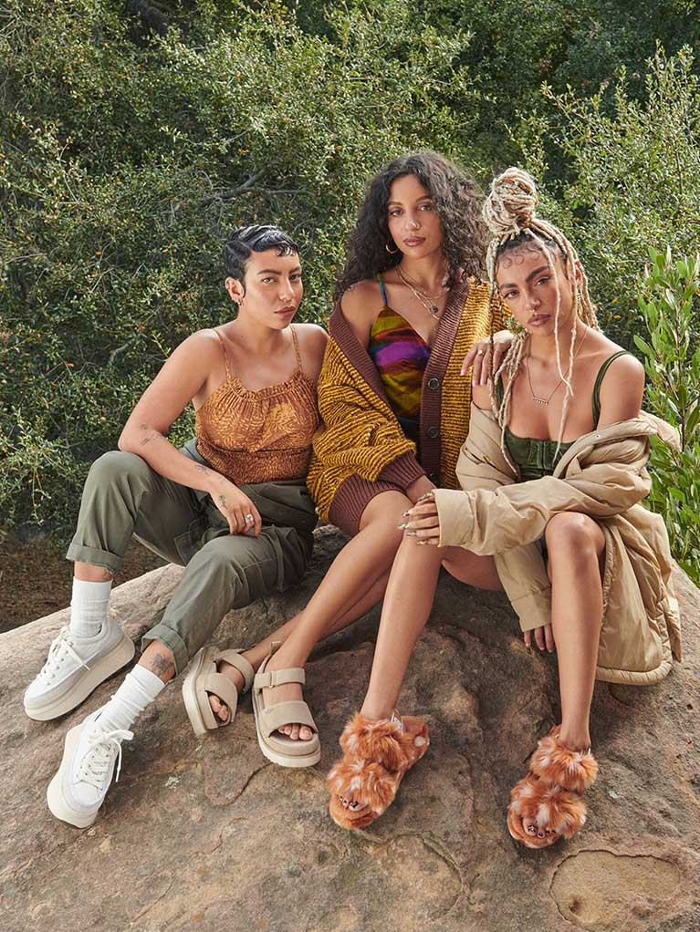 Three women in UGG shoes posing near a rock.