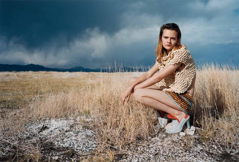Woman crouched in field wearing Eckhaus Latta light blue heel.