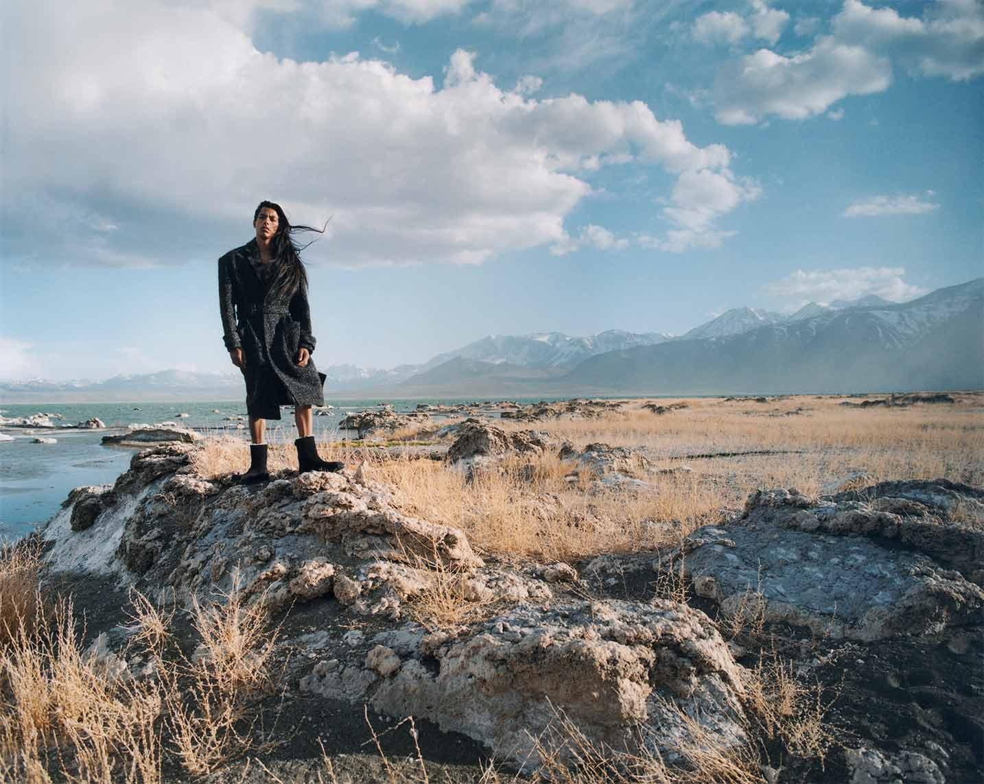 Man standing in field in black, Eckhaus boot.
