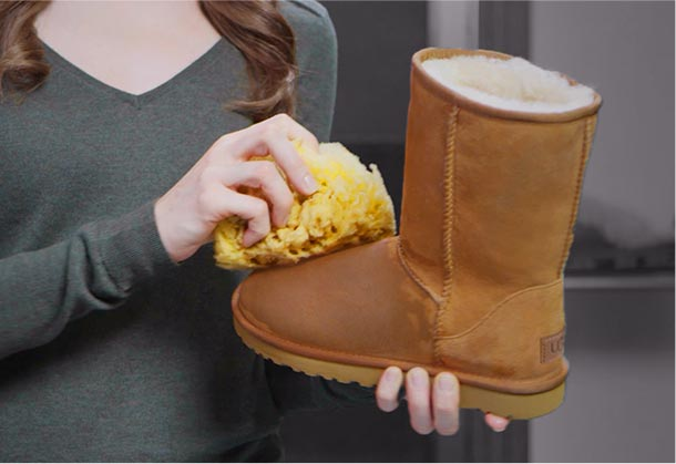 Woman damping Ugg classic with a sponge
