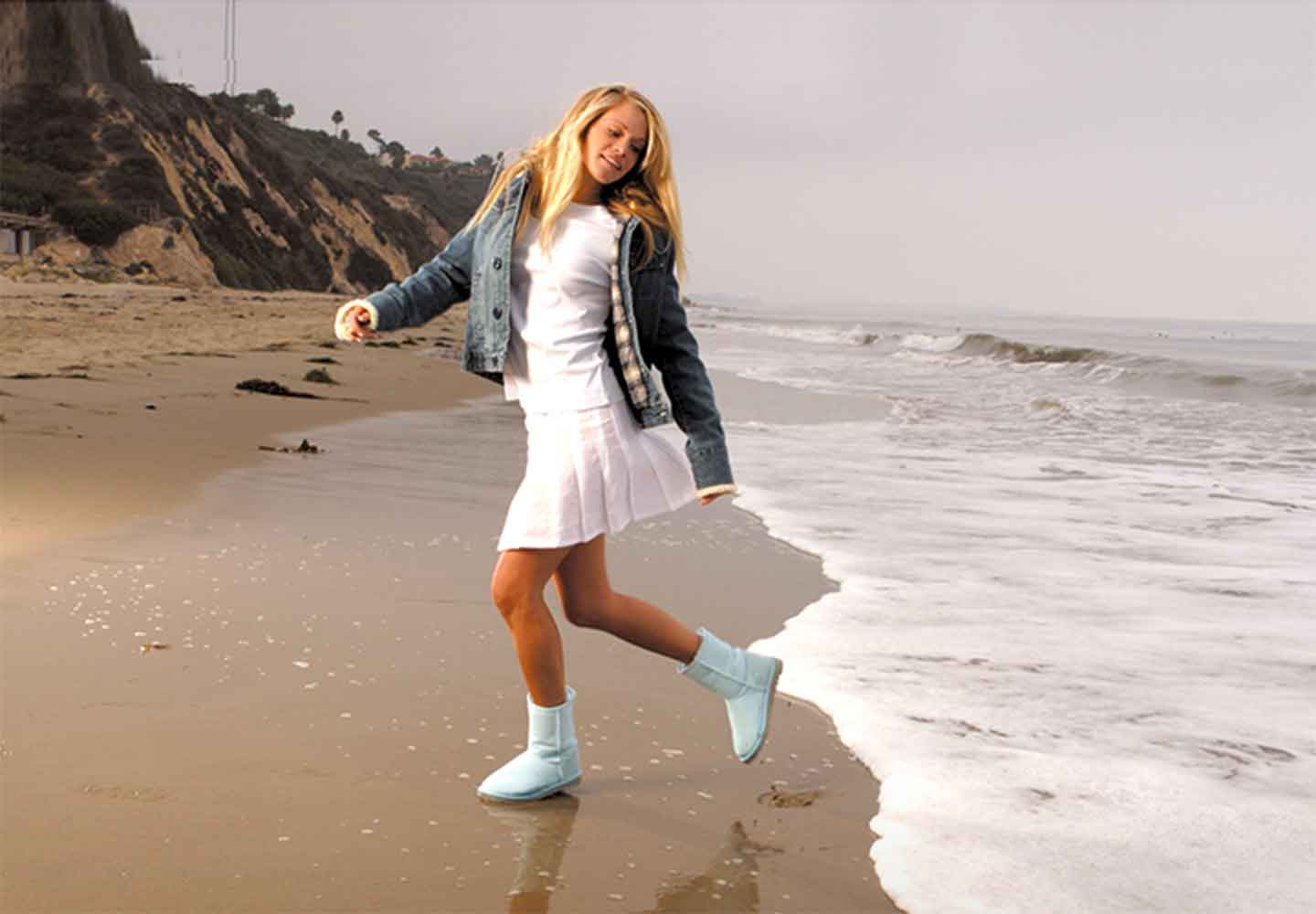 girl wearing Ugg classic boots on a beach