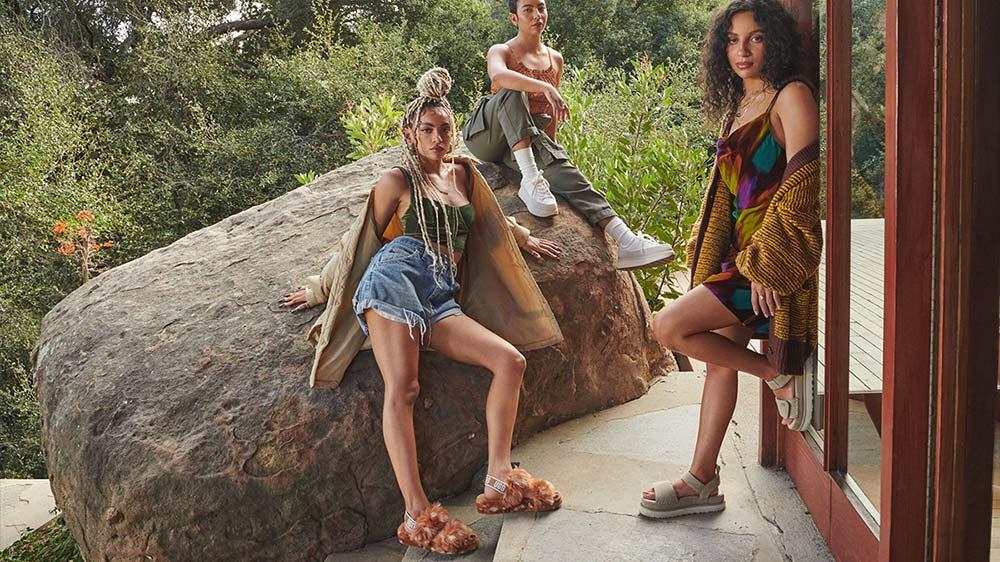 Three women in UGG shoes posing near a rock.