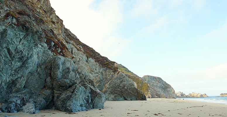 Rock wall jutting onto the beach shore and waves