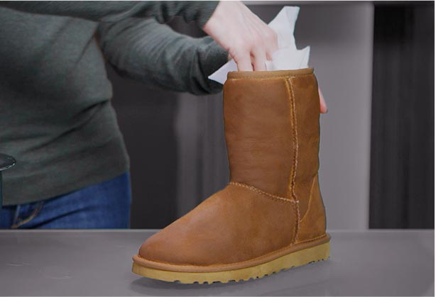 woman stuffing UGG classic with paper towels