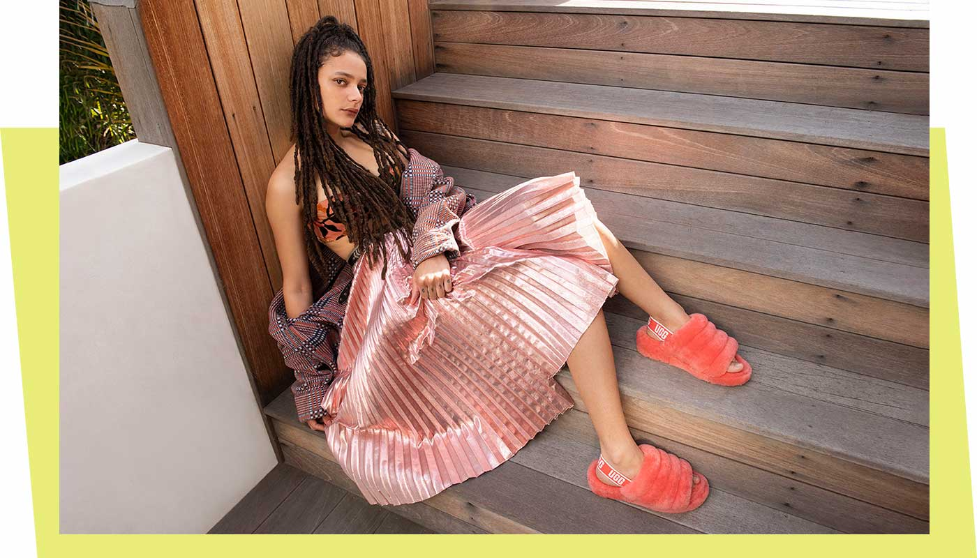Woman wearing Neon Fluff Yeah Slide Sandals sitting on stairs.
