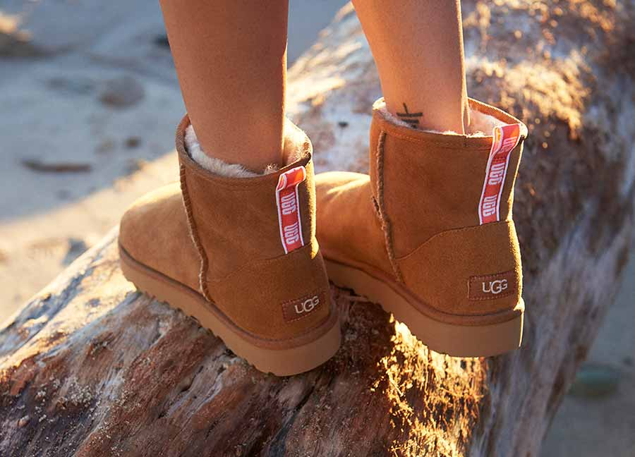 Close up of woman's feet wearing Neon Classic Mini II Boots standing on a log.