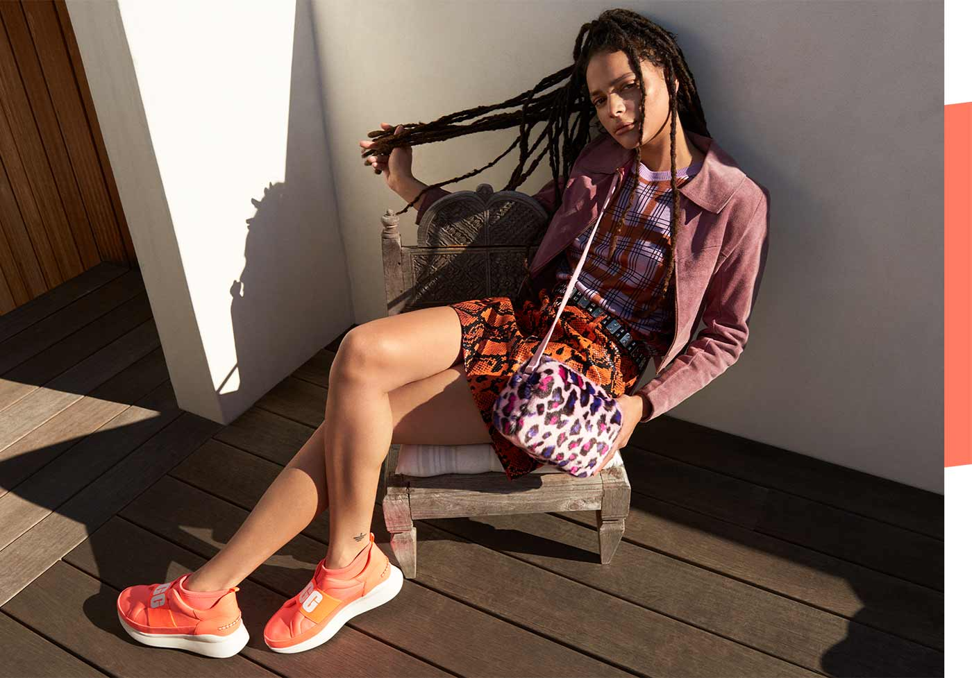 Woman wearing Neon Neutra Sneakers sitting on a chair.