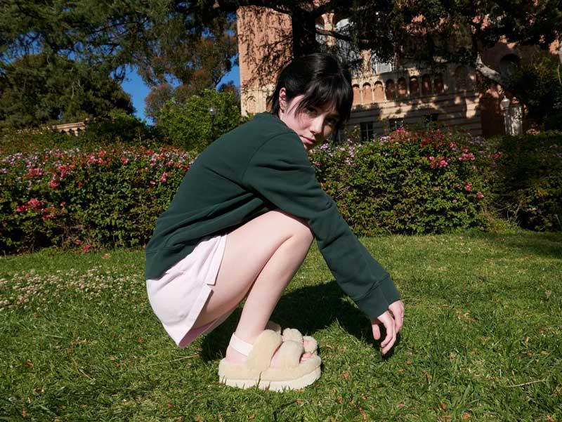 Collegiate model wearing white Oh Fluffita sandals.