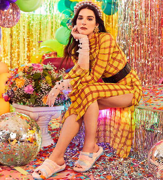 Influencer Hari Nef sitting in the party room wearing Fluff You Slippers.