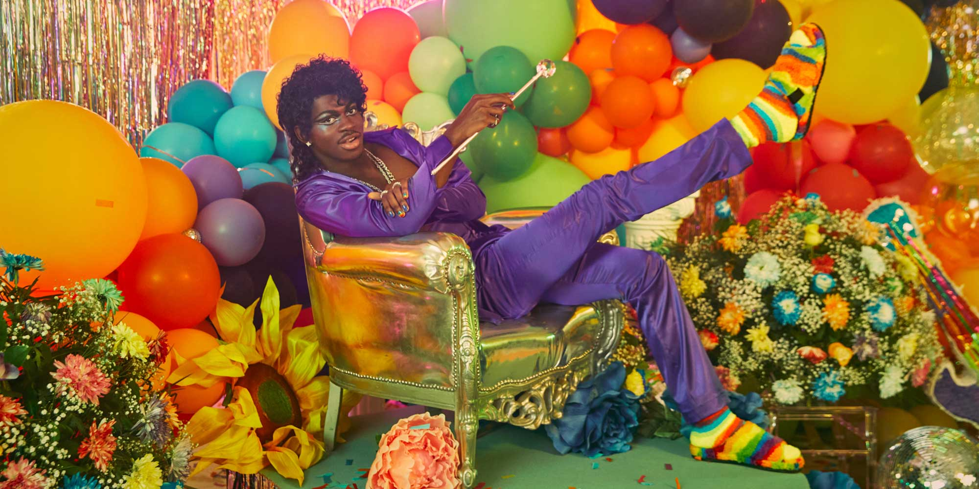 Lil Nas X wearing the new Pride collection sitting on the chair in a colourful backdrop.