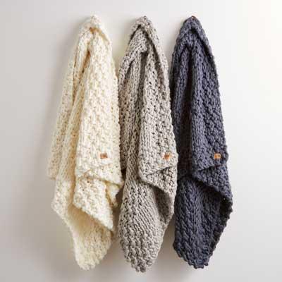 UGG shawls hanging on wall hook.