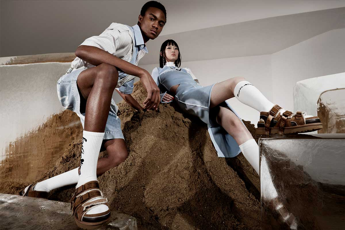 Two models on a mound of dirt wearing UGG boots by Feng Chen Wang
